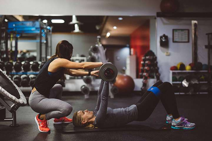 personal trainer with client lifting weights